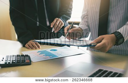 Business Worker Discussing Finance Graphs Report At Office.