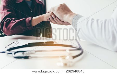 Doctor Consoles The Patient And Holding Hands With Medical Consultation At Hospital.