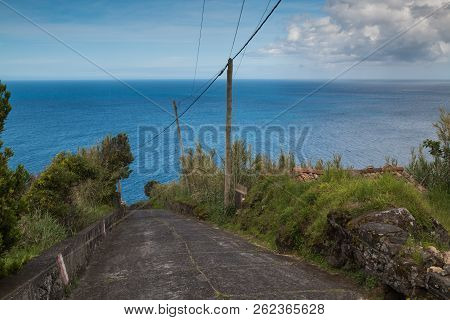 Old Coutry Road Down The Hill, Lined By Vegetation. Horizon Of Atlantic Ocean. Blue Sky With Some Cl