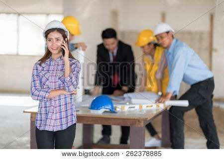 Engineer Woman Using Smartphone And Digital Tablet With Blurry Team Working Background.
