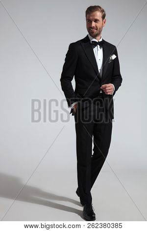 elegant man with hand in pocket walking and looking to side away from the camera on grey background