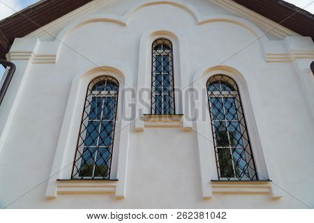 View Of The Church Wall Of White Stone With Three Windows.