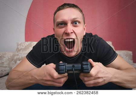 Angry gamer man with gamepad in the hands is playing in video game. Lose a game concept. poster