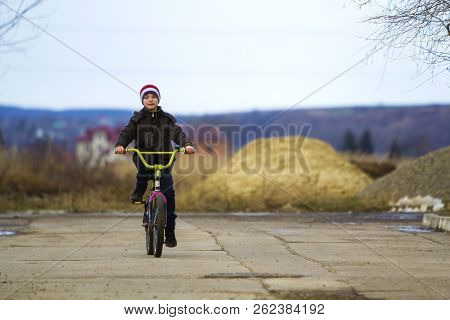 Little Boy Riding His Bicycle In Park Outdoors