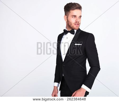 side view of curious man in tuxedo looking to side while standing on light grey background