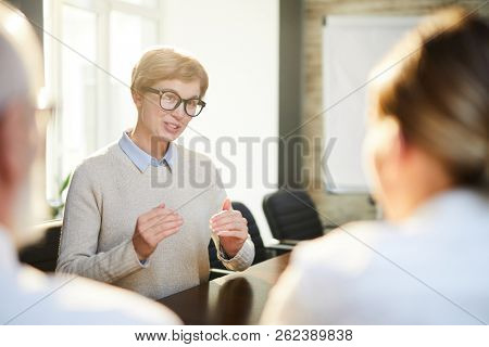 Young female applicant explaining something while answering question of employers during interview