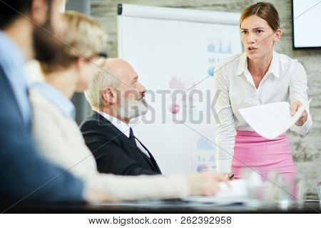 Scowling businesswoman in white shirt and pink skirt looking at one of colleagues while making report at seminar