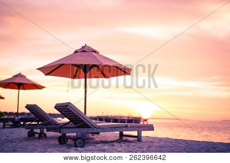 Sunset Beach Scene. Tranquil Tropical Landscape, Sun Beds And Umbrella. Colorful Orange And Yellow S