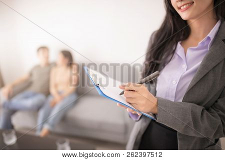 Agent Realtor In An Empty Apartment With Some Cilents Looking For Real Estate.