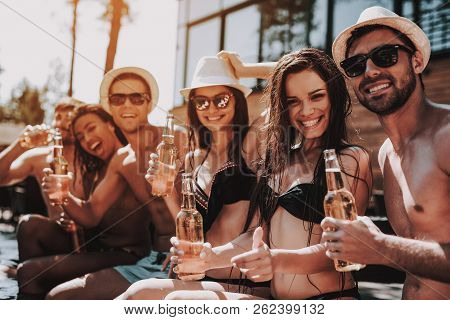 Young Friends With Alcoholic Drinks At Poolside. Group Of Young Smiling People Holding Bottles Of Be