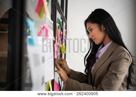 Creative Businesswoman Putting Her Ideas On Glass During A Presentation In Meeting Room. Setup Studi