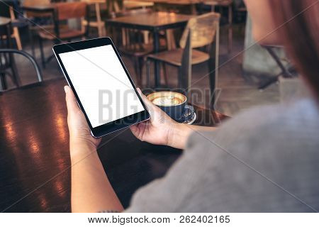 Mockup Image Of Woman's Hands Holding Black Tablet Pc With Blank White Screen With Coffee Cup On Woo