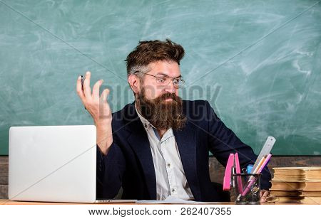 Not Sure In Knowledge. Examiner Full Of Doubts Sit At Table Chalkboard Background. Tricky Examinator