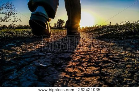 The Silhouette Of The Feet Of A Person Walking West Or East Towards The Sun Along A Dirt Road Across