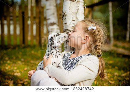Cute Girl Kissing Her Puppy, Doggy On The Wood Fence Background.happy Girl With A Dog Licking Her Fa