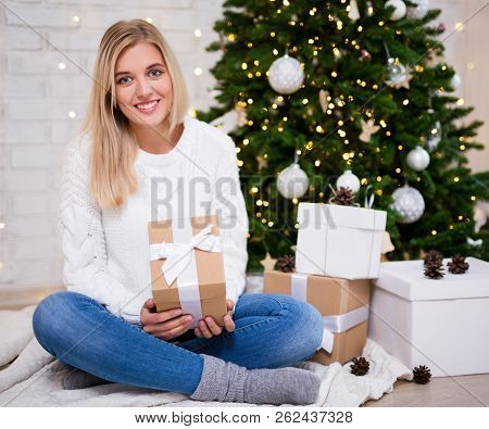 Young Woman Sitting In Living Room With Decorated Christmas Tree And Gift Boxes
