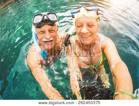 Happy Retired Couple Taking Selfie In Tropical Sea Excursion With Water Camera And Snorkel Masks - B