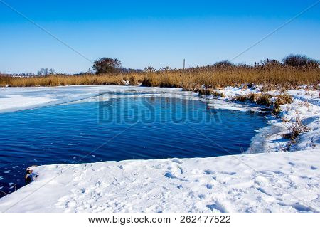 A Sunny Winter Day On The River. Shore The Rivers Covered With Snow. The Blue Water Of The River Ref