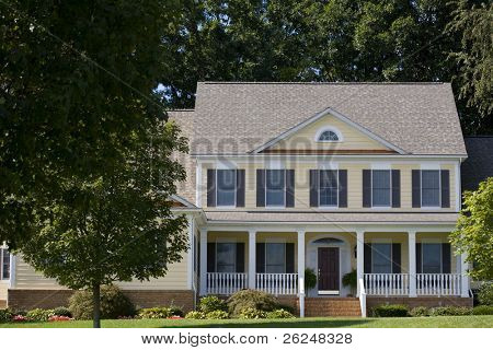 Yellow colonial home with shutters