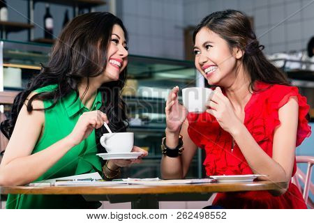 Two female best friends talking and sharing memories while drinking together a cup of coffee in a trendy location