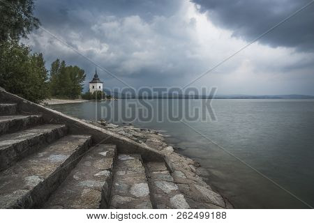 Rocky Beach With Church On Liptovska Mara Lake In Slovakia With Stone Stairs In Foreground