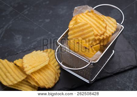Thick ridge cut potato chips served in frying basket