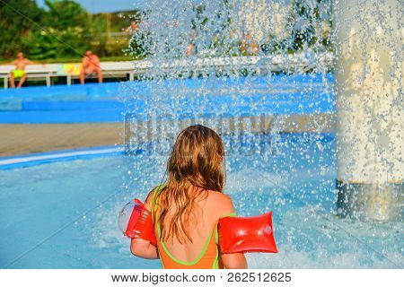 Happy Little Girl Enjoying Summer Day In The Swimming Pool. Girl Going To A Sprinkler In  Spray Pool