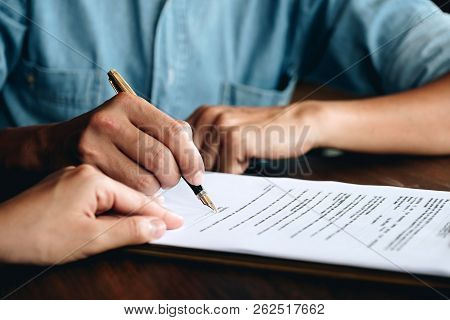 Business Man Signing A Contract. Close Up Of Two Business Partners Signing A Document For Agreement
