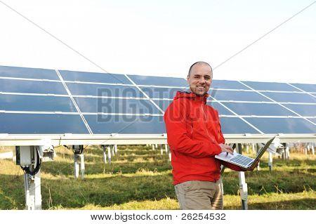 Ingenieur mit Laptops, Solar-Panels im Hintergrund