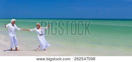 Panoramic web banner happy senior man and woman couple dancing and holding hands on a deserted tropical beach with bright clear blue sky