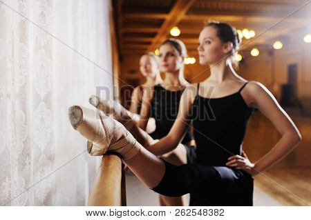 Three Young Cute Ballerinas Perform Exercises On A Choreographic Machine Or Barre