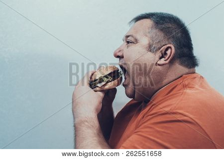 Hungry Fat Mat In Oranfe T-shirt With Burger. Man With Bulimia. Unhealthy Lifestyle Concept. Man Wit