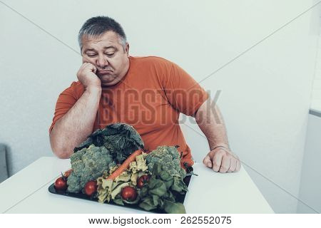 Fat Upset Man With Tray With Vegetarian Food. Man With Bulimia. Unhealthy Lifestyle Concept. Sitting