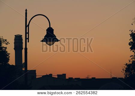 Sunset Over City Roofs. Sunset In City. Sunset Over The Roofs. Lamppost Silhouette In Sunset. Dusk I