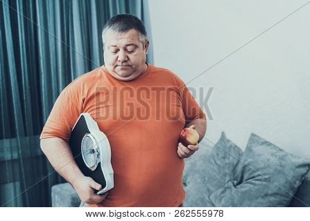 Fat Man I T-shirt With Weighter And Apple In Hands. Man With Bulimia. Unhealthy Lifestyle Concept. S