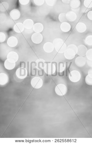 Abstract Background Of Metallic Black And White Holiday Bokeh Lights With Free Space For Text.
