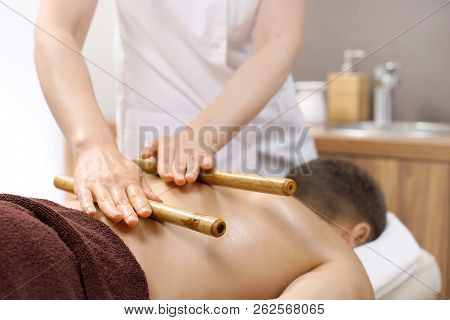 Relaxing Massage With Bamboo Chopsticks.  The Masseur Massages The Body Using Bamboo Sticks.