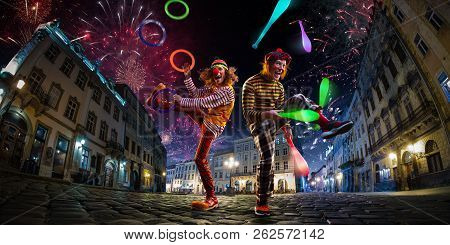 Night Street Circus Performance Whit Two Clowns, Juggler. Festival City Background. Fireworks And Ce