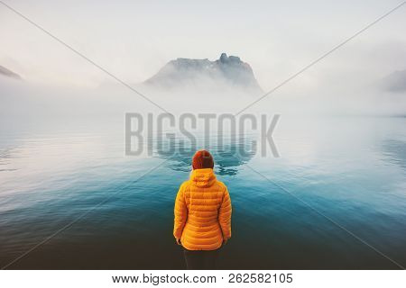 Woman alone looking at foggy sea traveling adventure lifestyle outdoor solitude sad emotions winter down jacket clothing cold scandinavian minimal landscape poster