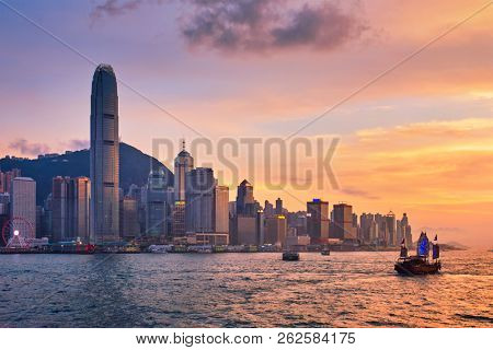Hong Kong skyline cityscape downtown skyscrapers over Victoria Harbour in the evening with junk tourist ferry boat on sunset with dramatic sky. Hong Kong, China
