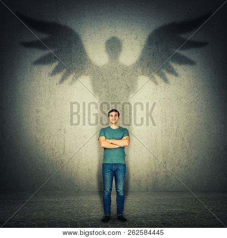 Casual Confident Man Arms Crossed. Full Length Portrait Casting A Superhero Shadow With Angel Wings