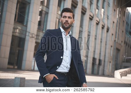 Confident Businessman. Confident Young Man In Full Suit Adjusting His Sleeve And Looking Away While