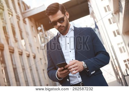 Businessman Wearing Suit And Using Modern Smartphone Near Office At Early Morning, Successful Employ