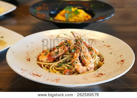 Healthy food concept. Spaghetti with shrimps, prawns, chopped basil and tomato on white plate. Blur plates with foods background.