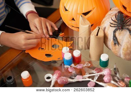 Close-up View Of Unrecognizable Child Sitting At Table With Pumpkins And Painting Diy Paper Mask Whi