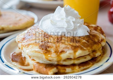Plate Of Pancakes With Whipped Cream And Vanilla And Caramel Syrup
