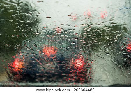 Blurred View Of Cars In Traffic Through Car Windshield Covered In Rain Drops