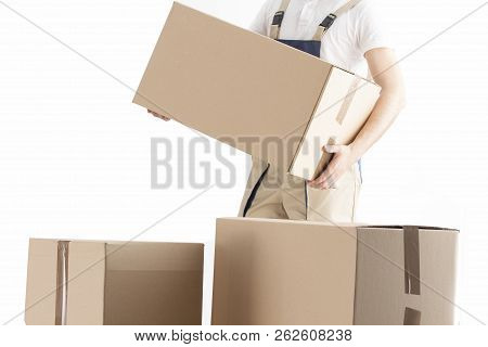 Delivery Man Puts Cardboard Box. Relocation Service Concept. Loader With Box. Mover In Uniform.