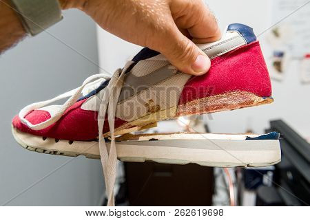 Male Hang Holding One Sport Footwear Sneaker With Broken Sole - Quality Manufacturing Problems And N