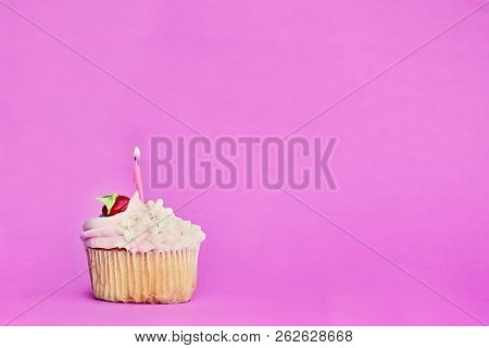 Pretty Strawberry Or Cherry Flavored Frosted Cupcake Decorated With White Chocolate Shavings And One